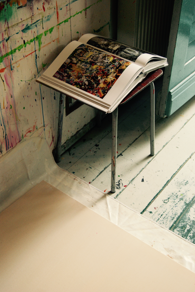 an art book on a stool in a studio with  walls and floor, next to it a white canvas