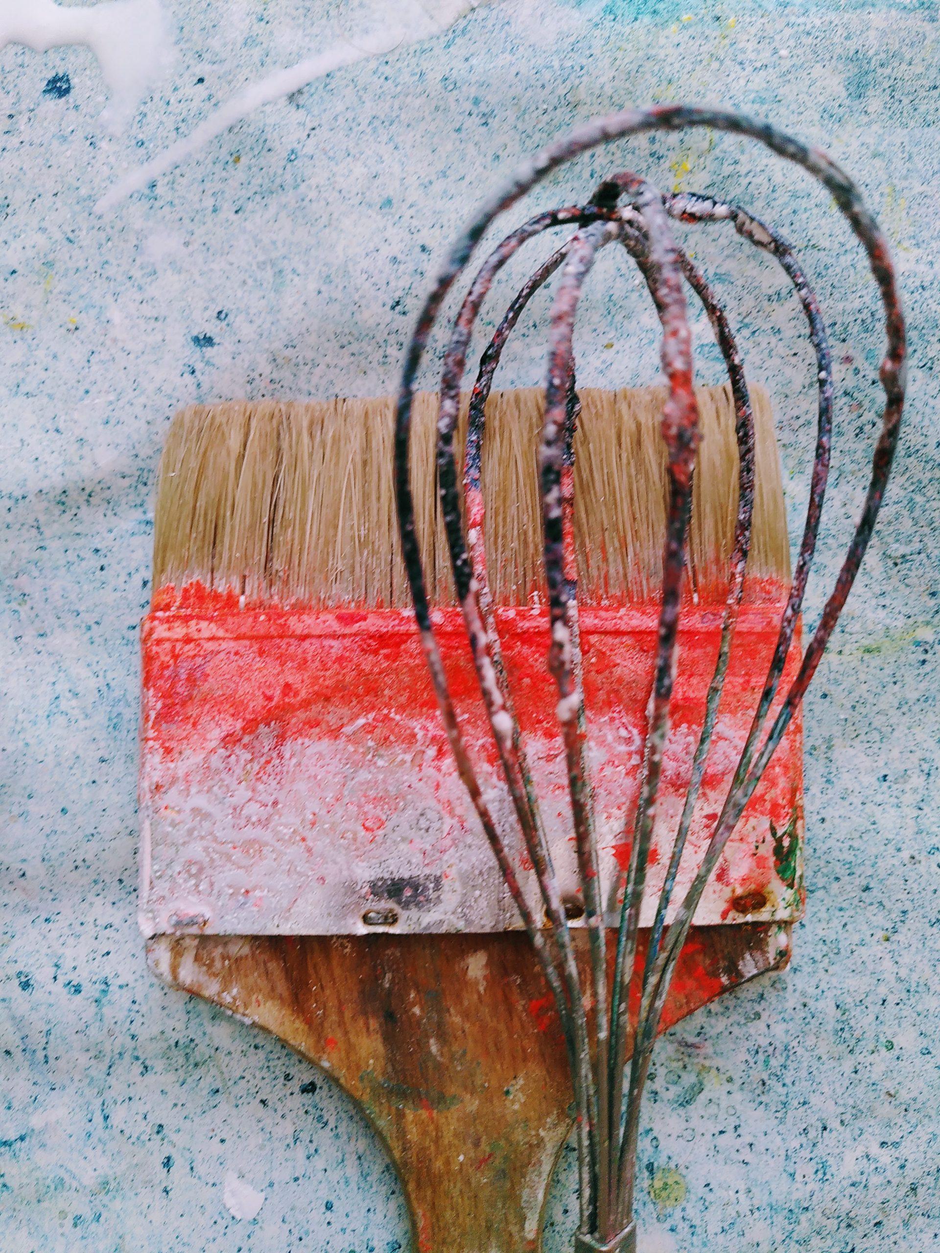 Pinsel und Rührbesen mit Farbspuren auf Atelierboden