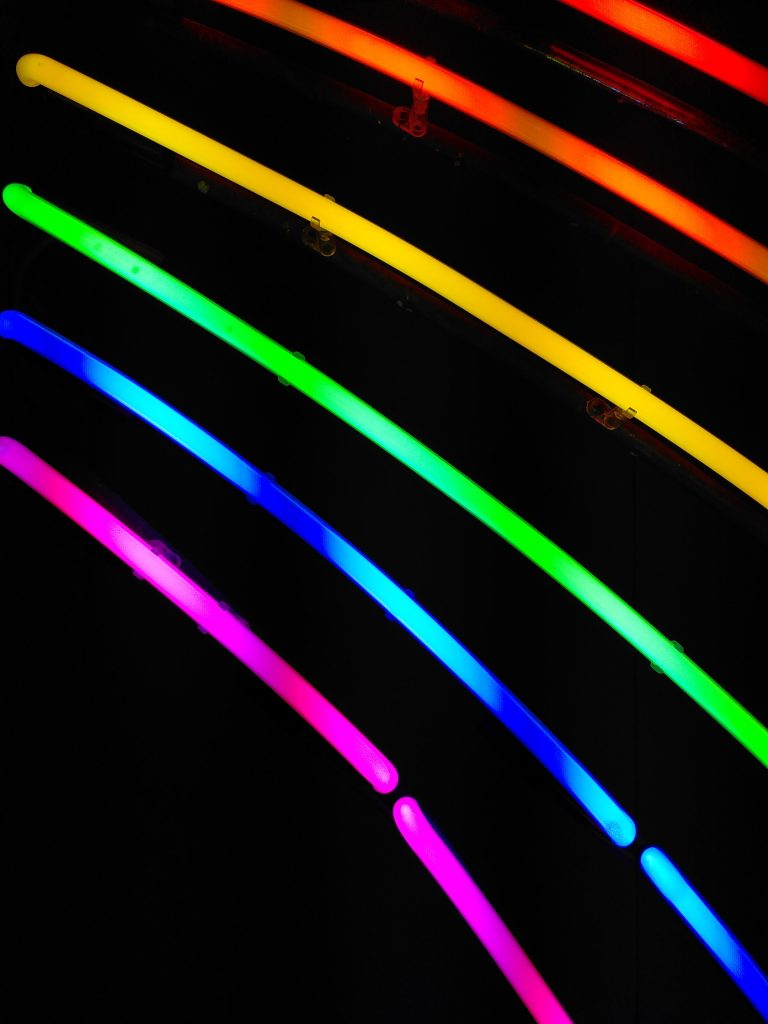 rainbowcolored neonlights infront of a dark background