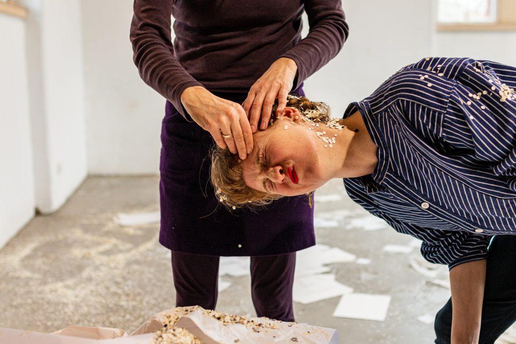 Performance Situation: Hände berühren Kerstins Gesicht, das mit Konfetti bedeckt ist und eine Grimasse zieht