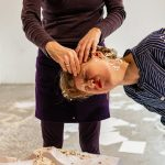 Performance Situation: Simones Hände berühren Kerstins Gesicht, das mit Konfetti bedeckt ist
