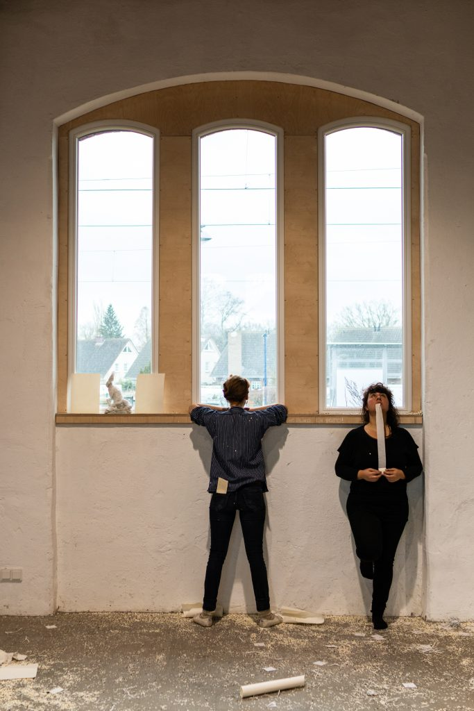 performance situtation: two women standing at a window looking in different directions, one out of the window, the other into the room