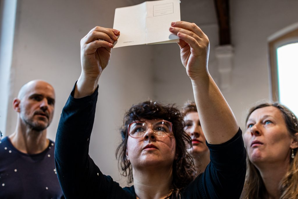 performance situation: four people looking up to a paper notebook one of them is holding up