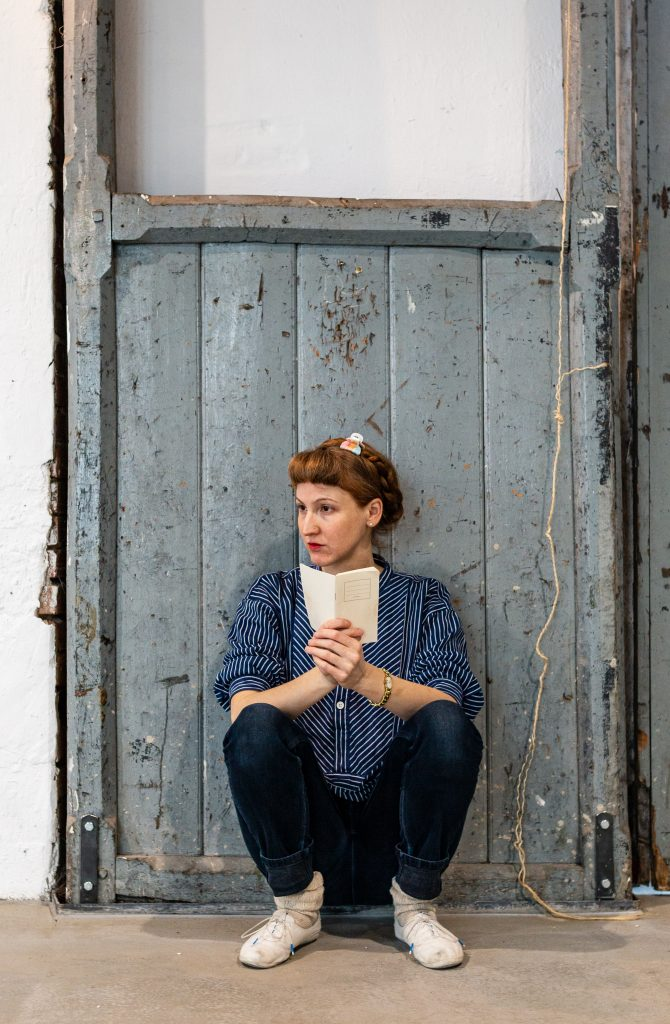 Kerstin is sitting in a squat position in front of a wooden gate, holding a white notebook in her hands and observes