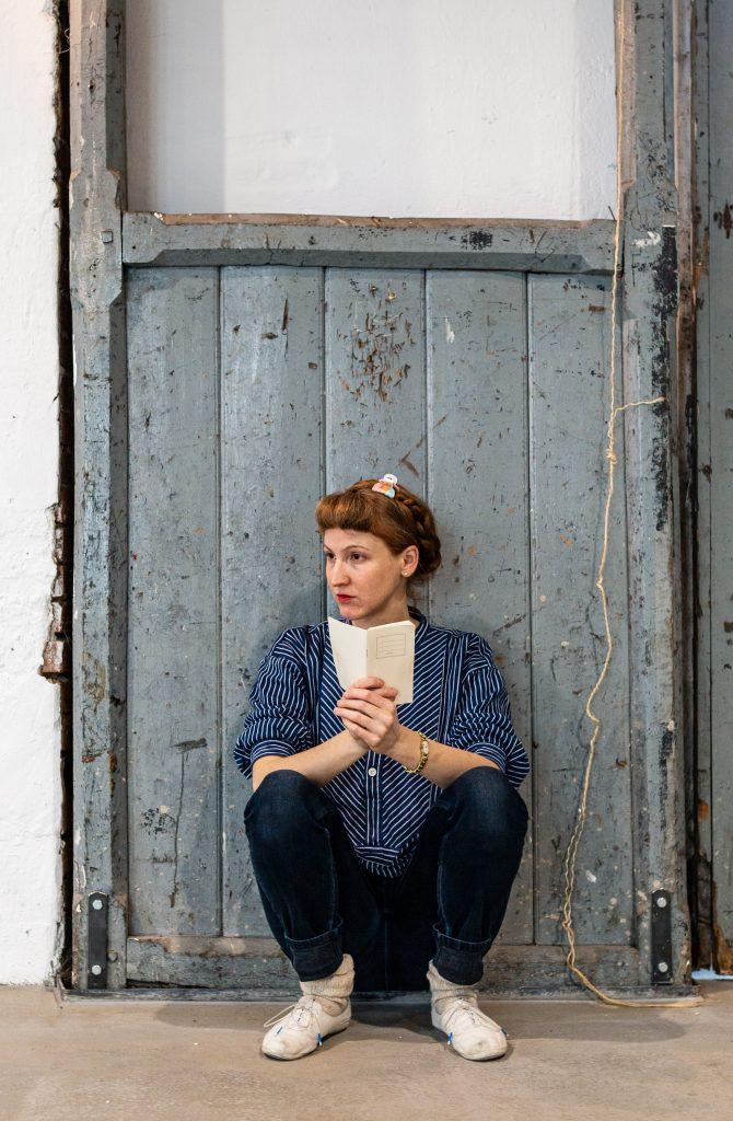 Kerstin sitzt in der Hocke vor einem Holztor, hält ein weißes Notizbuch in den Händen und beobachtet