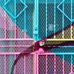 ein Gittertor aus Metall, das in cyan, rosa und gelb angesprüht ist