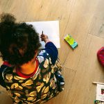 a child sits on the floor holding a color pencil over a white sheet of paper
