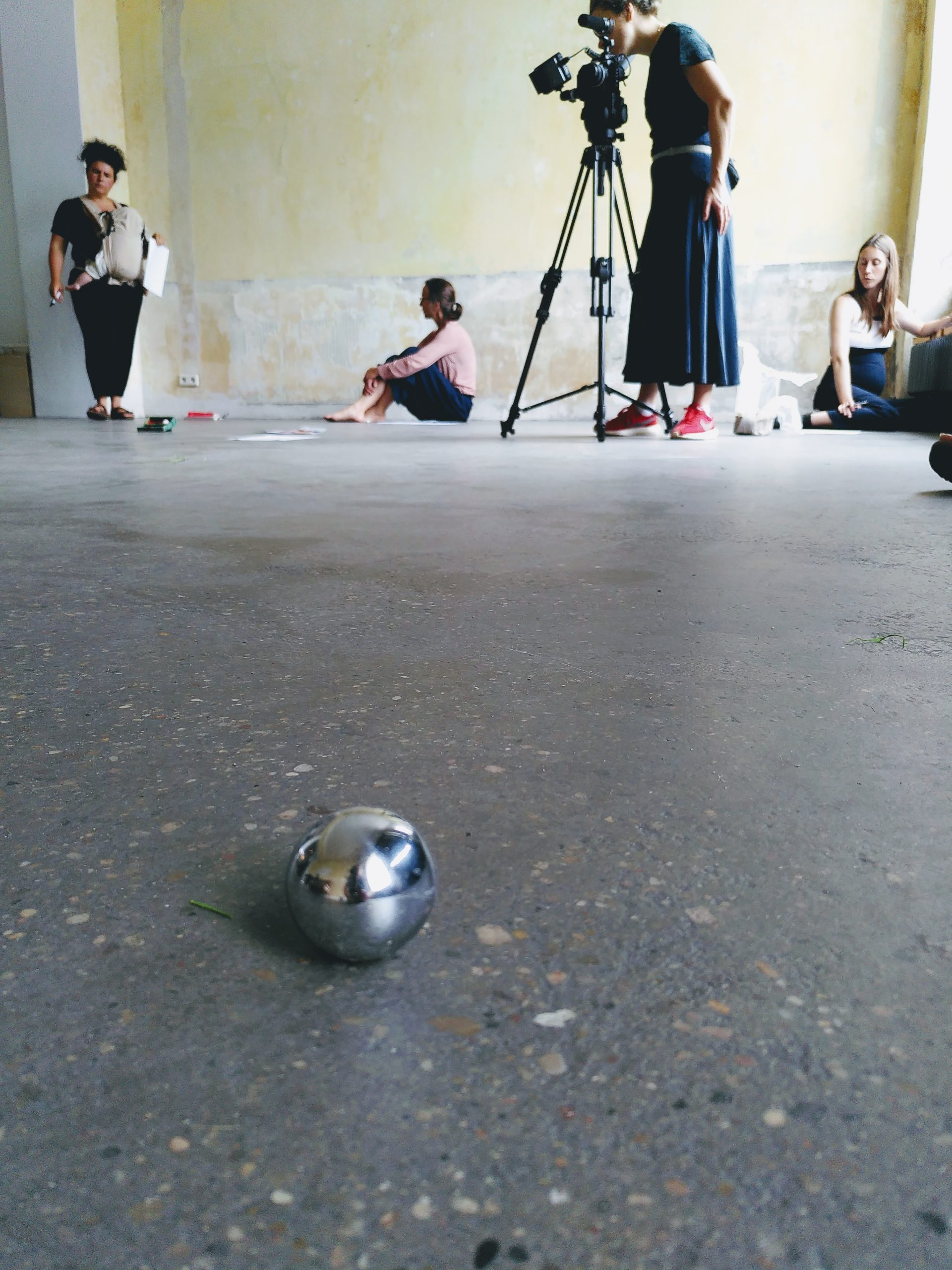 A silver sound ball on stone floor, behind it standing a person with tripod and camera, a standing person with child and two sitting persons