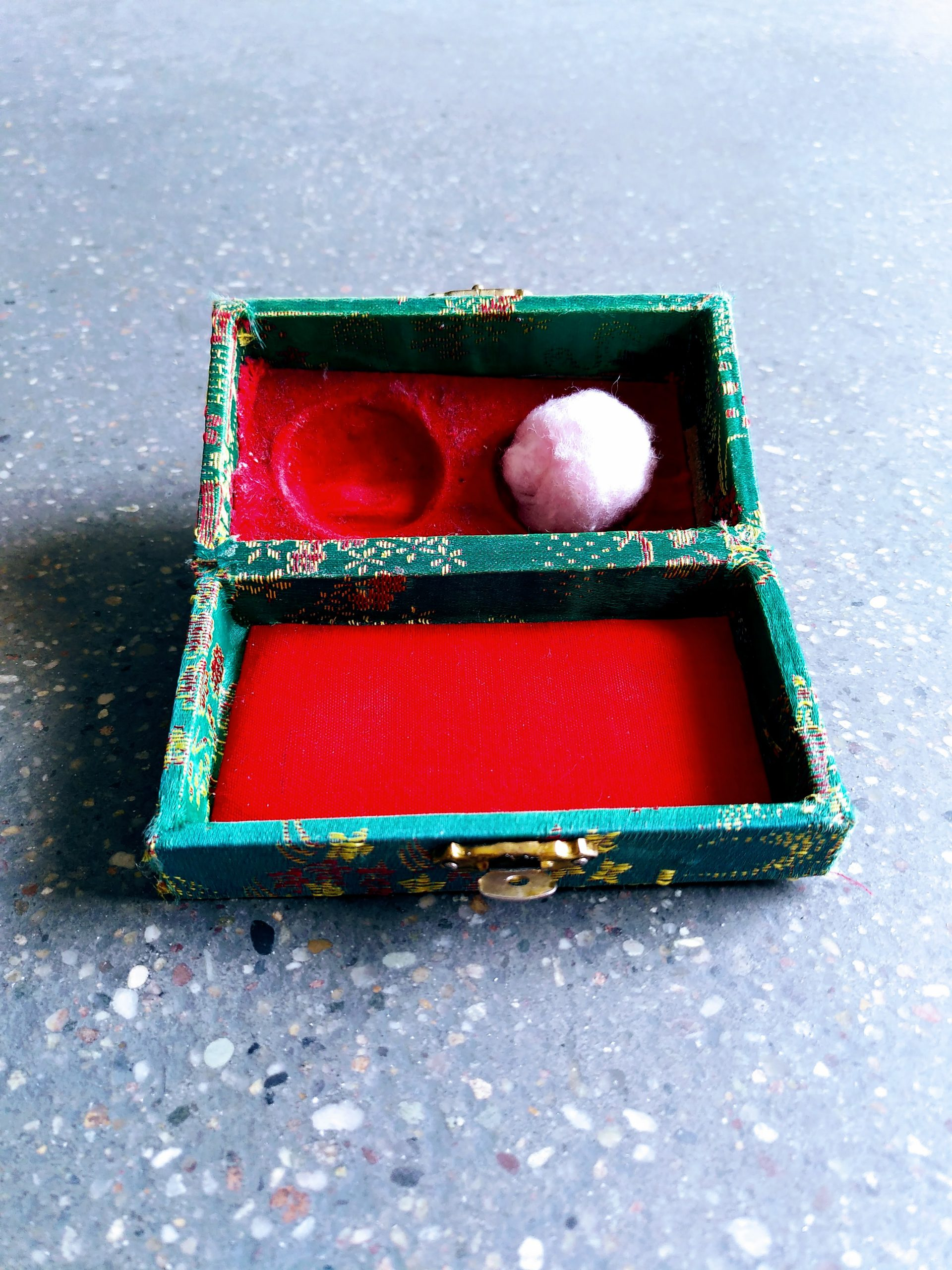 A green box with red lining. In it lies a pink cotton ball.