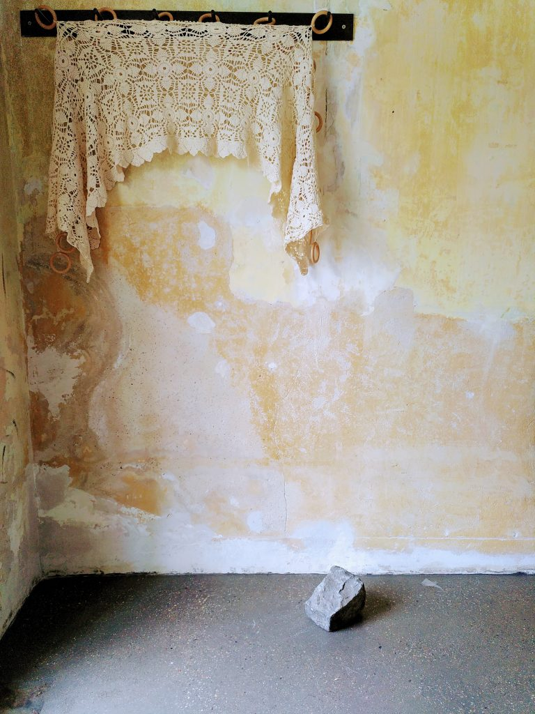 An einer Garderobe hängt eine Häkelgardine. Dahinter eine gelbe Wand. Am Boden davor liegt ein schwerer Stein. | On a coat rack hangs a crochet curtain. Behind it a yellow wall. On the floor in front of it lies a heavy stone.