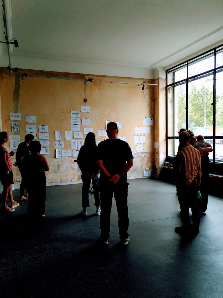 Mehrere Menschen betrachten eine Resonanzwand, an der Papierblätter mit Zeichnungen und Text hängen. | Several people look at a resonance wall on which paper sheets with drawings and text hang.