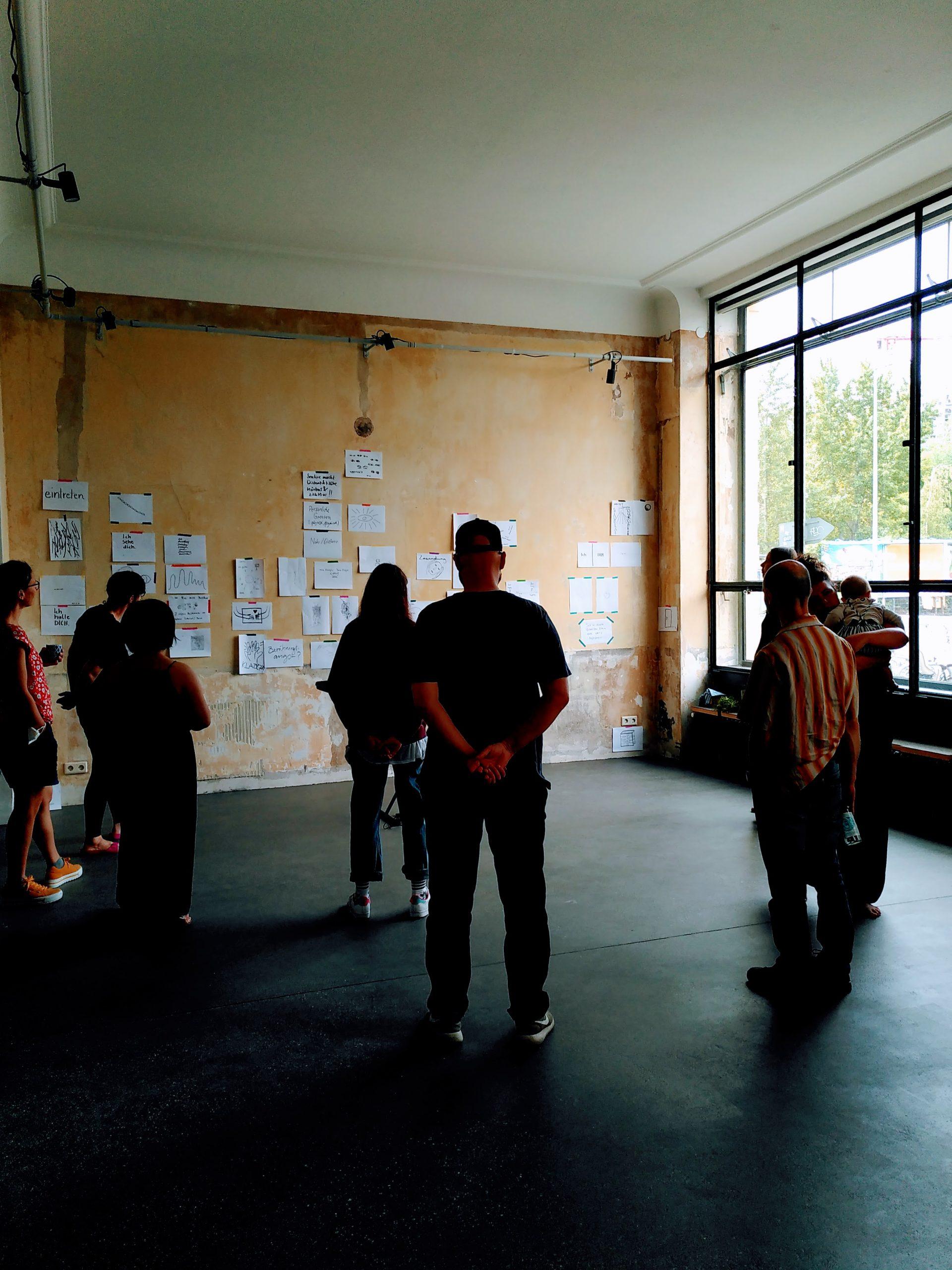 Mehrere Menschen betrachten eine Resonanzwand, an der Papierblätter mit Zeichnungen und Text hängen.