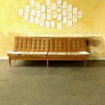 Ein Sofa steht vor einer gelben Wand. Darüber hängen gezeichnete Portraits | A sofa stands in front of a yellow wall. Above are drawn portraits