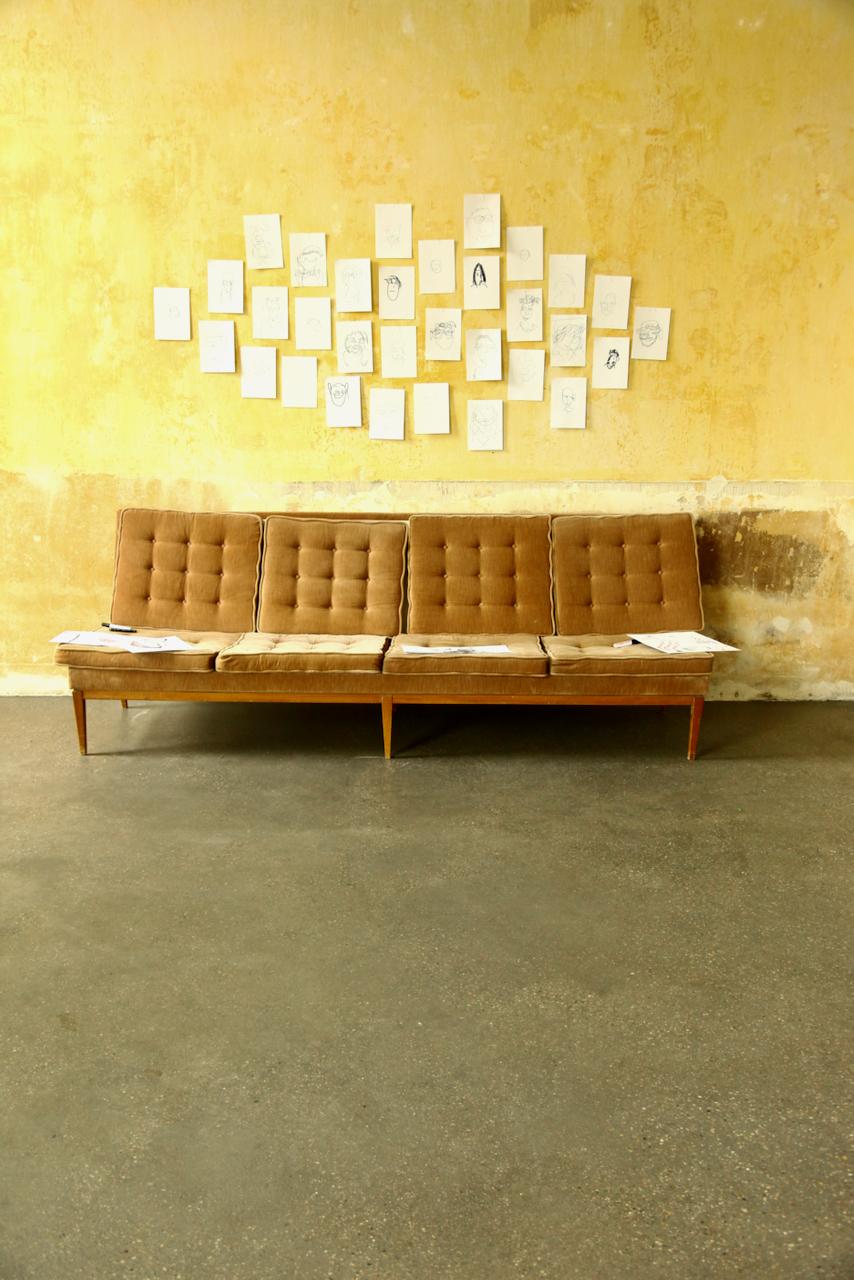 Ein Sofa steht vor einer gelben Wand. Darüber hängen gezeichnete Portraits