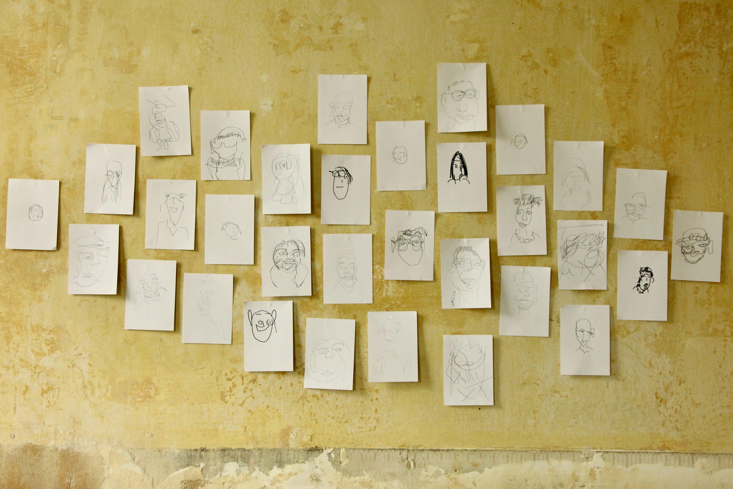 Gezeichnete Portraits hängen an einer gelben Wand