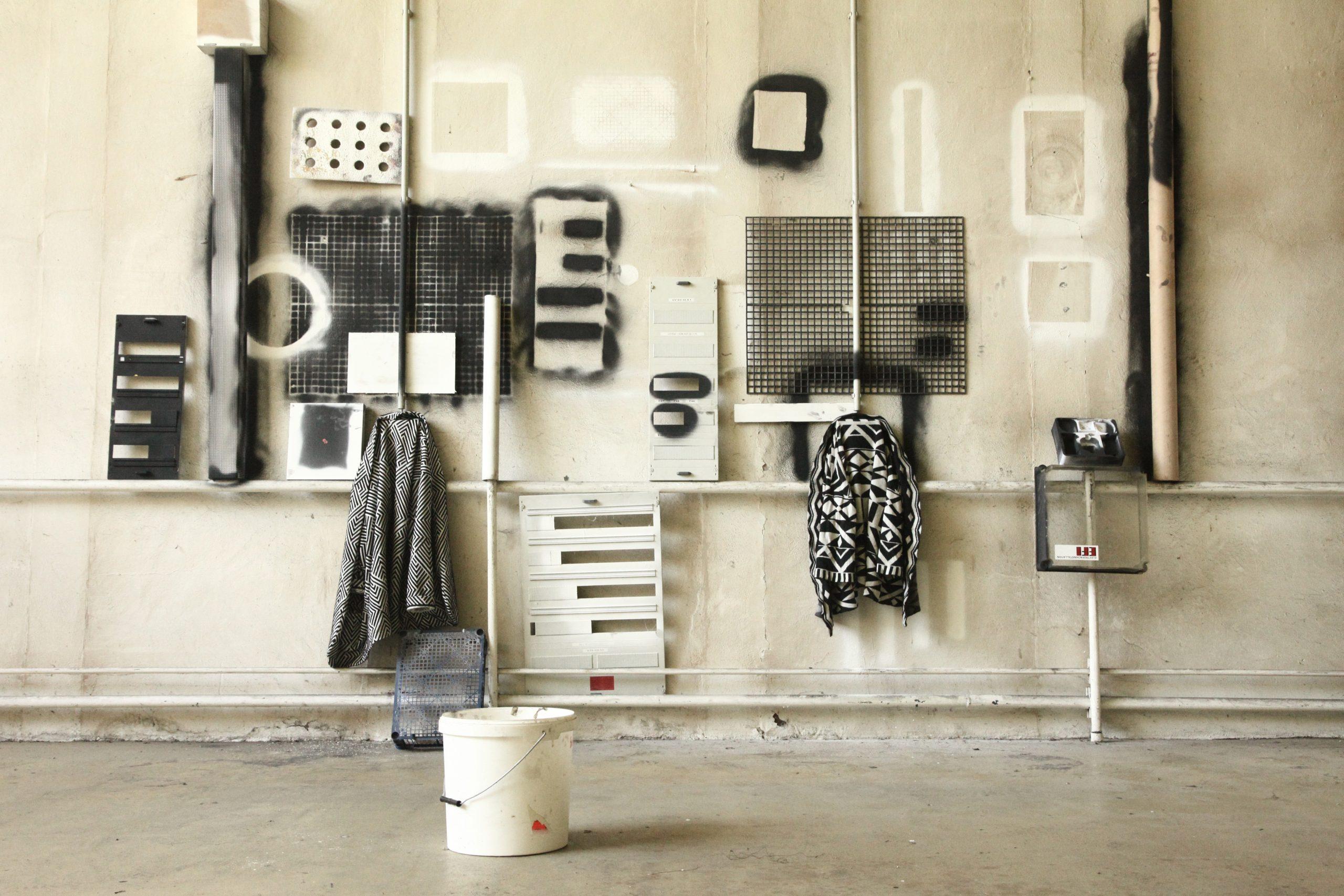 vor einer mit schwarz und weiß besprühten Wand sind ebenfalls schwarze und weiße Gegenstände zu einer Komposition arrangiert | in front of a wall sprayed with black and white, black and white objects are arranged into a composition