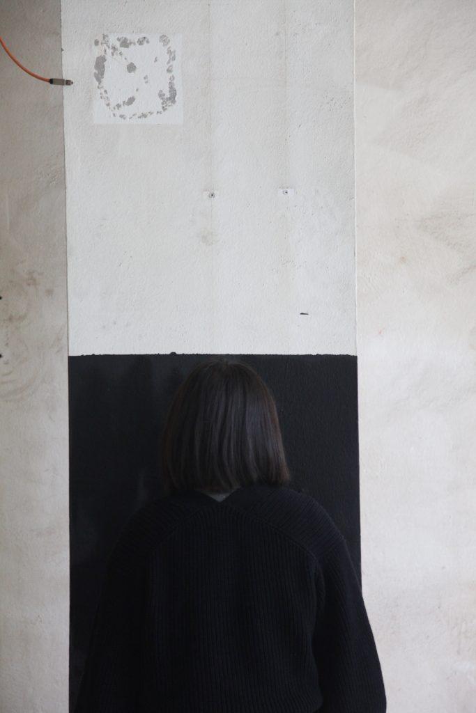 vor einer schwarz-weißen Säule steht eine schwarzbekleidete Person mit schwarzen Haaren, die mit dem Hintergrund verschmilzt | in front of a black and white column stands a person dressed in black with black hair that merges with the background