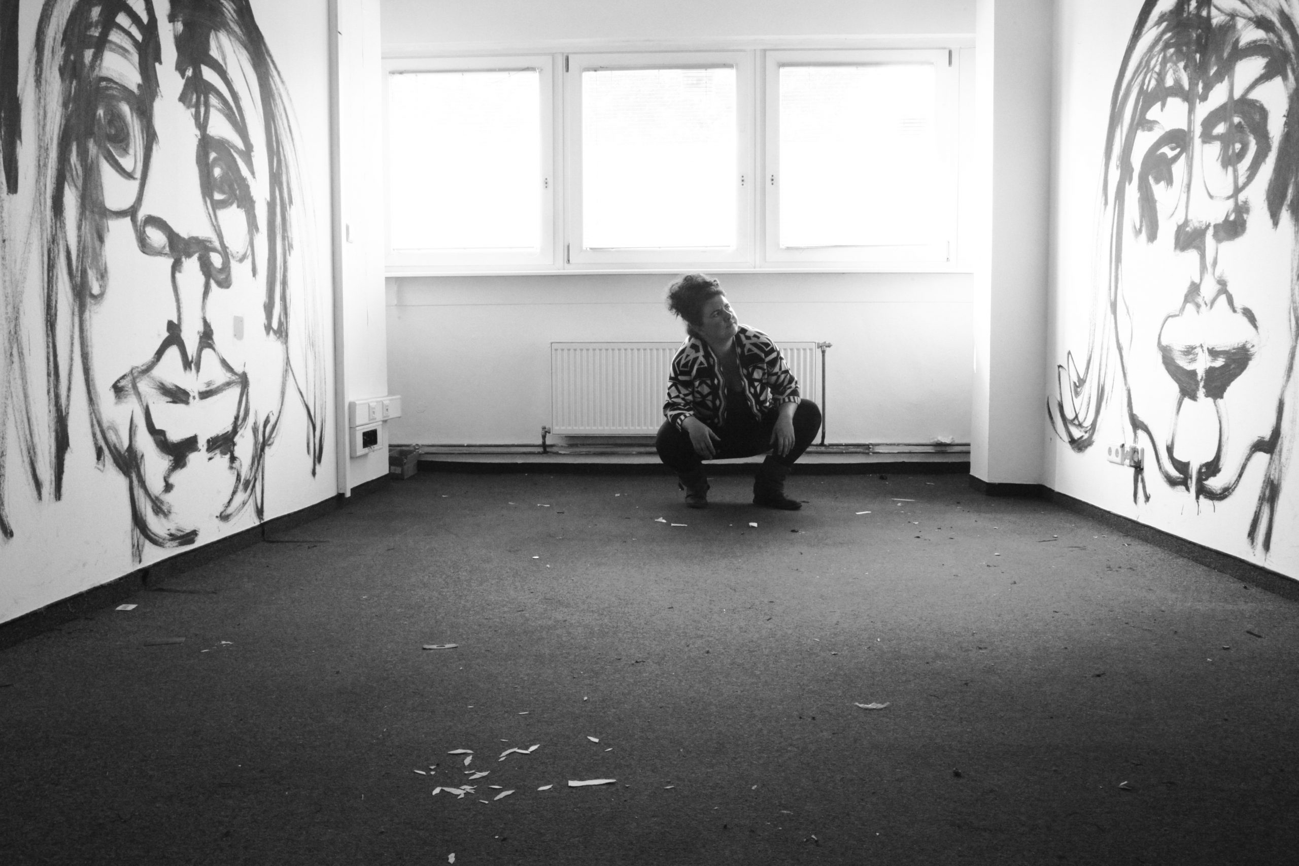 eine Person hockt in einem Raum, rechts und links neben ihr an der Wand sind überlebensgroße Portraits gezeichnet | a person squats in a room, to the right and left of him on the wall are drawn larger-than-life portraits