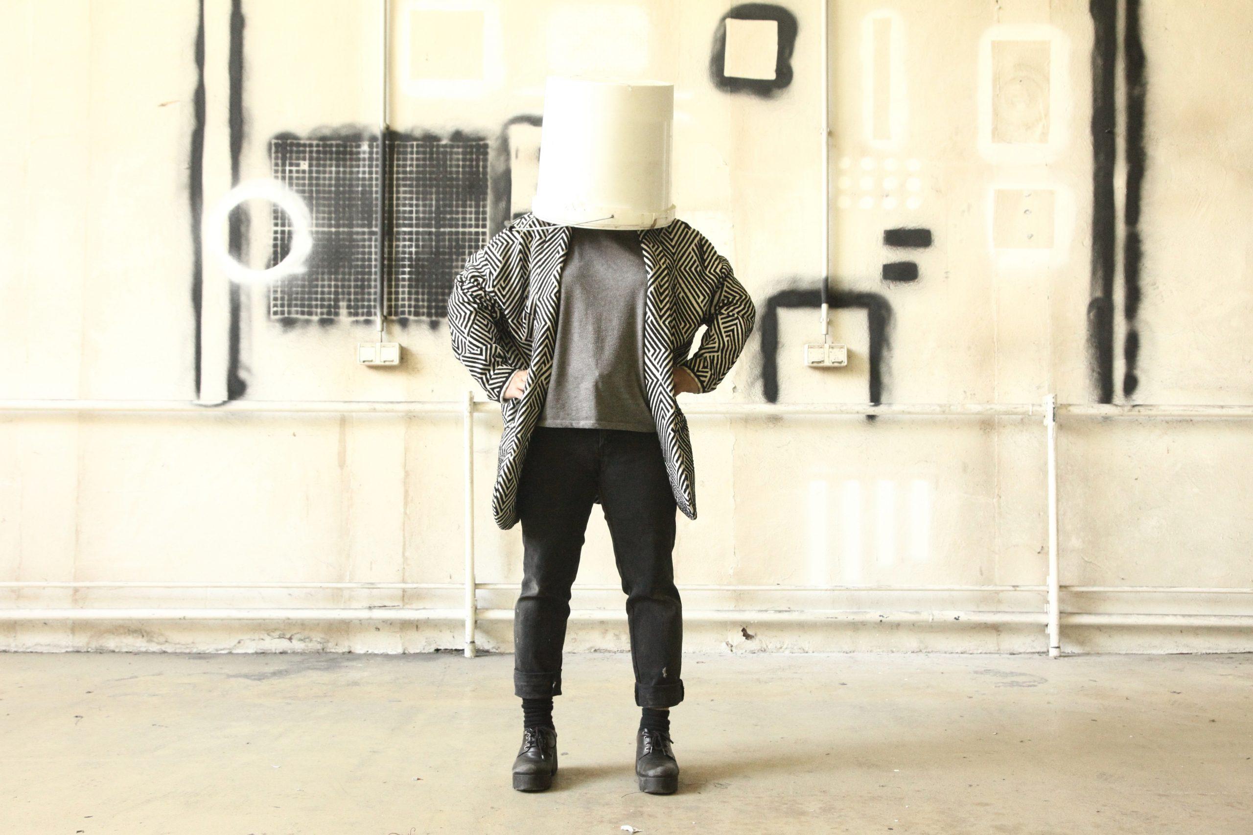 eine Person hat einen weißem Eimer über den Kopf gestülpt und steht, die Hände in die Hüften gestützt vor einer schwarz-weiß bemalten Wand | a person has a white bucket over his head and stands with his hands on his hips in front of a black and white painted wall