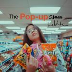 eine Person in einem Laden trägt mehrere Packungen Süßigkeiten. darüber steht der Text The Pop-up Institute