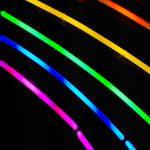 Regenbogenfarbene Neonleuchten vor dunklem Hintergrund