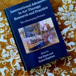 """The book """"International advances in art therapy research and practice"""" lying on a brown and white patterned blanket"""